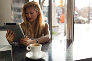 Beautiful young woman using her digital tablet in cafe