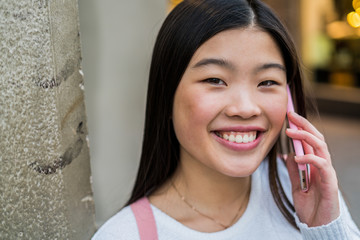 Chinese young woman calling with her pink cellphone in the streets of Barcelona