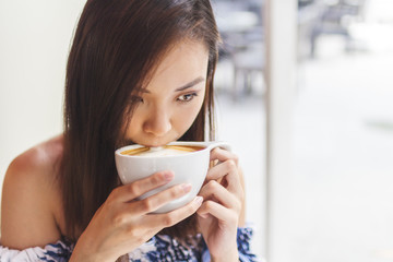 Young Chinese Woman Drinking A Cup Of Coffee