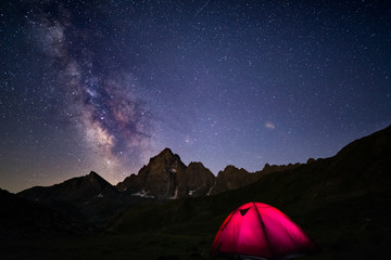 Camping under starry sky and milky way at high altitude on the Alps. Illuminated tent in the foreground and majestic mountain peak in the background. Adventure and exploration in summertime.