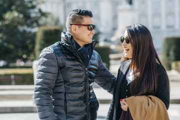 Chinese tourist couple walking around la almudena ana palacio real in Madrid