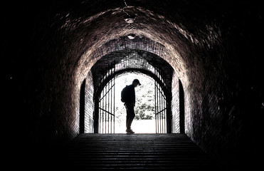 Teenager at the end of a dark tunnel