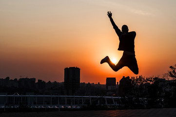 Silhouette of a young man on sunset background