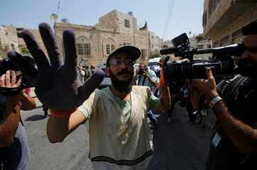 An Israeli settler blocks cameras during a protest by Palestinians in the old city of the West Bank city of Hebron