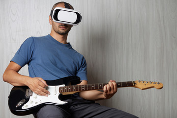 young adult playing guitar at home using viewer for augmented reality