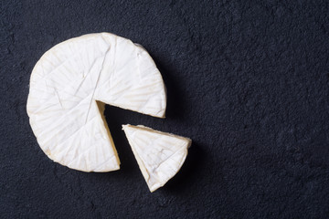 Cheese brie on dark stone background