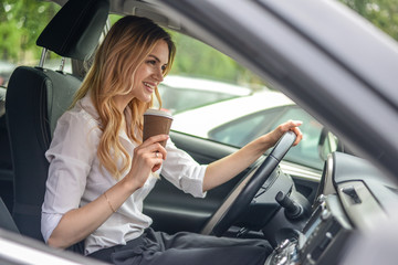 A woman is car holding coffee to go