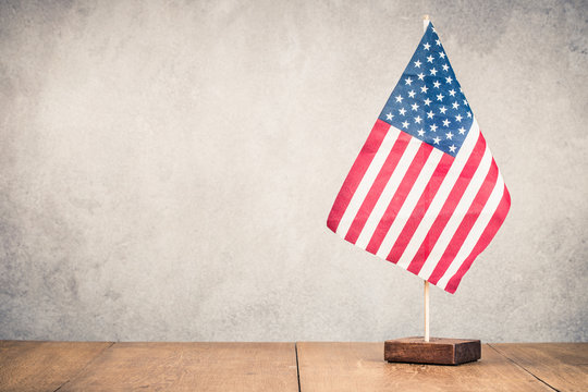 Retro USA flag on wooden table front old concrete wall background. Vintage style filtered photo