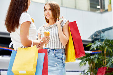 Portrait of two beautiful girls shopping in mall, chatting happily holding paper bags and eating ice cream