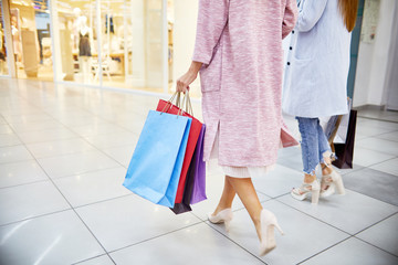 Low section portrait of two beautiful young women wearing coats and high heels walking in shopping mall holding paper bags with purchases