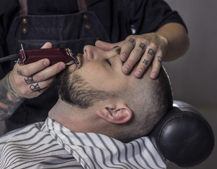close up of Master making beards correction in barbershop salon