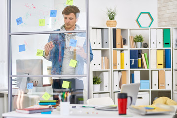 Portrait of young man dressed in casual clothes planning startup project drawing graph on glass wall
