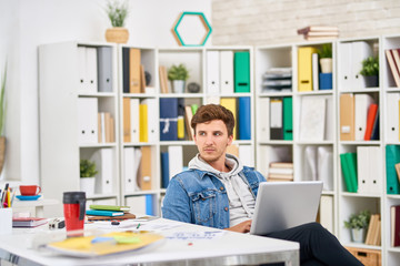 Portrait of pensive young man dressed in casual clothes using laptop while working in creative office space