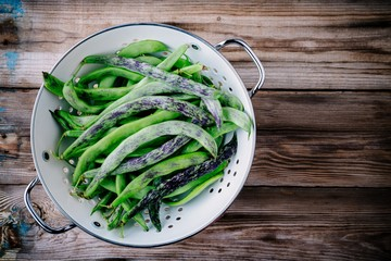 fresh raw french green beans on a wooden background