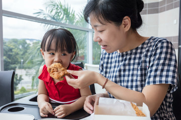 Asian Chinese mother and daughter eating fried chicken