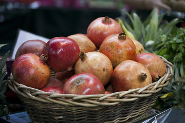 the Ripe pomegranates in a wicker basket on the counter in the market for sale.