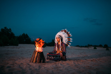 Young American Indian woman against fire