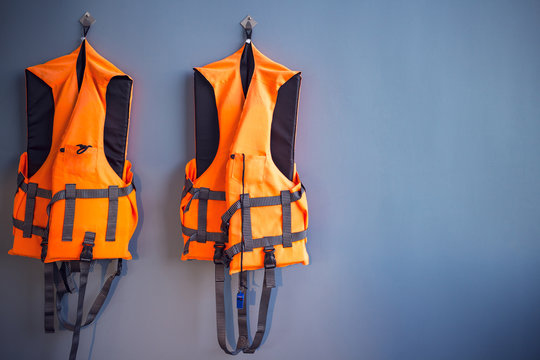 orange life jackets hanged on plain grey wall by swimming pool for emergency, filter effect