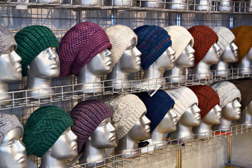 Woolen hats on silvery heads of mannequins in store