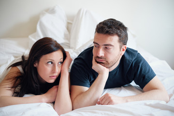 Worried and bored lovers couple after a fight lying in bed