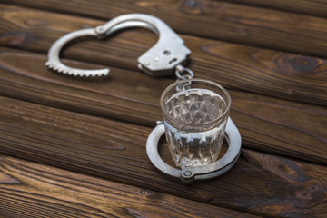 Glass of alcohol with handcuffs. A glass of vodka drinking and driving