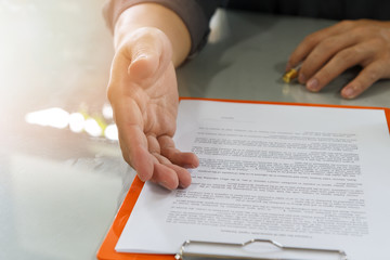 Businessman offering contract paper to his business partner for sign contract