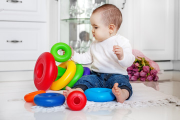 The baby is fond of toys at home. The concept of childhood development and lifestyle.