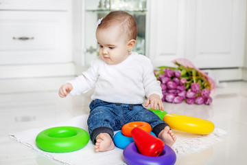 The baby is playing a developing toy. Child under 1 year. The concept of childhood development and lifestyle.