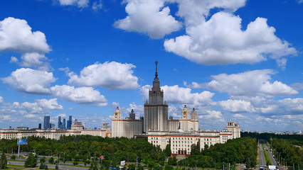 Wide angle panoramic landscape view of dramatic clouds over the sunny summer campus of Lomonosov Moscow State University under blue sky