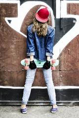 Cute girl in a baseball cap with a skateboard on a dark background.Sport.
