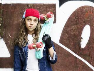 Cute girl in a baseball cap with a skateboard on a dark background.Sport.