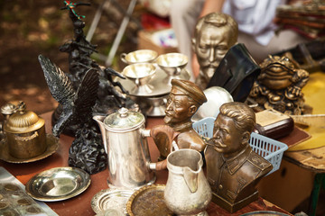 USSR famous historic persons busts and metal tableware at a flea market. Many old vintage things at a garage sale