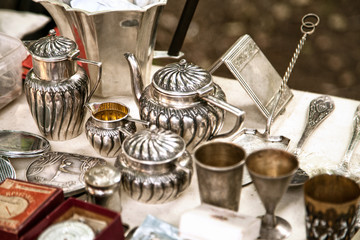 Antique silver teapots, creamer and other utensils at a flea market. Old metal tableware collectibles at a garage sale Wall mural