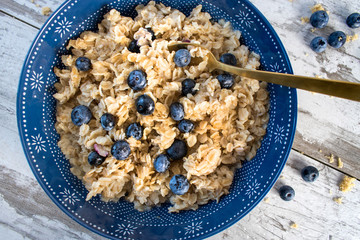 Closeup of Oatmeal with Blueberries in blue bowl on rustic table