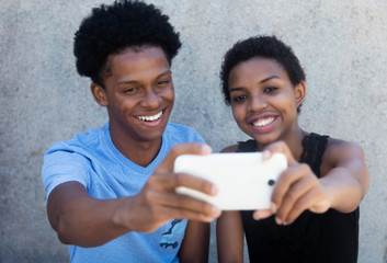 Joyful laughing african american couple taking selfie with phone