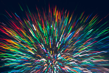 Abstract background of colorful lines in motion on black. Bokeh of defocused curves, blurred rainbow neon leds, festive backdrop of holidays, fireworks and salute