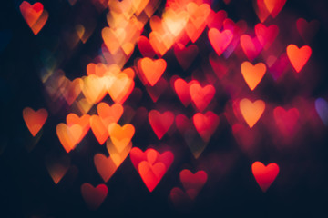 Abstract background of colorful hearts on black backdrop. Bokeh of defocused glitters, blurred pink and orange symbols of love. Festive wallpaper of holidays and celebrations, St. Valentine's day