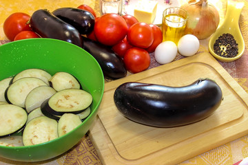Sliced eggplant on a cutting board and soaked in salted water in a bowl. Fresh vegetables for cooking light dinner, Moussaka - a traditional Greek dish step by step cooking process