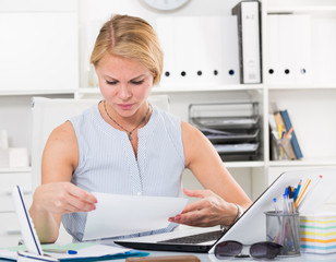portrait of  woman working with documents and laptop and having problems at company office