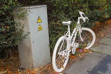 The modern phenomenon of a memorial Ghost Bike chained to a post at the scene of a tragic fatal accident involving a motor vehicle and a cyclist on the road to Bangor Co Down from Belfast