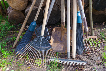 Old dirty garden tools (cultivator, shovel, rake)