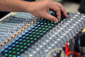 The remote sound engineer. Remote control of the sound engineer shallow depth of field. The DJ uses a mixing console