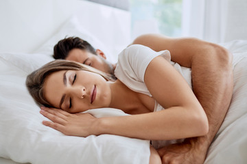 Side view of gorgeous young woman sleeping while her husband is hugging her