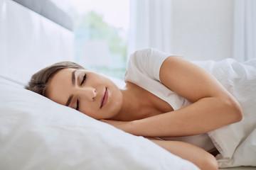 Portrait of beautiful young woman sleeping in bedroom