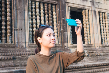 Female traveler selfie with her smartphone in angkor wat siem reap cambodia