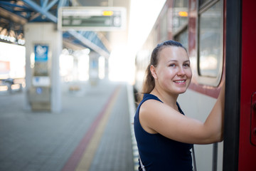 Young brunette woman waves goodbye / farewell from the train, smilling