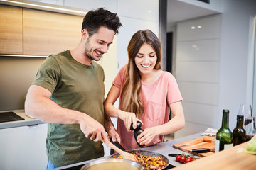 Cute joyful couple cooking together and adding spice to meal, laughing and spending time together in the kitchen