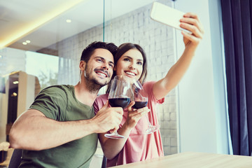Attractive young couple sitting at table and taking photo holding glass of wine