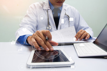 Medicine doctor in white gown working with digital tablet at table  in the hospital