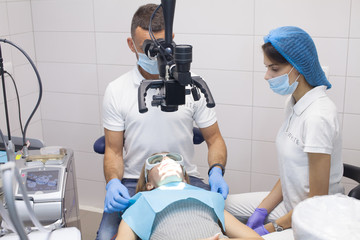 Young female patient visiting dentist office.Beautiful woman with healthy straight white teeth sitting at dental chair with open mouth during a dental procedure.Dental clinic. Dental caries